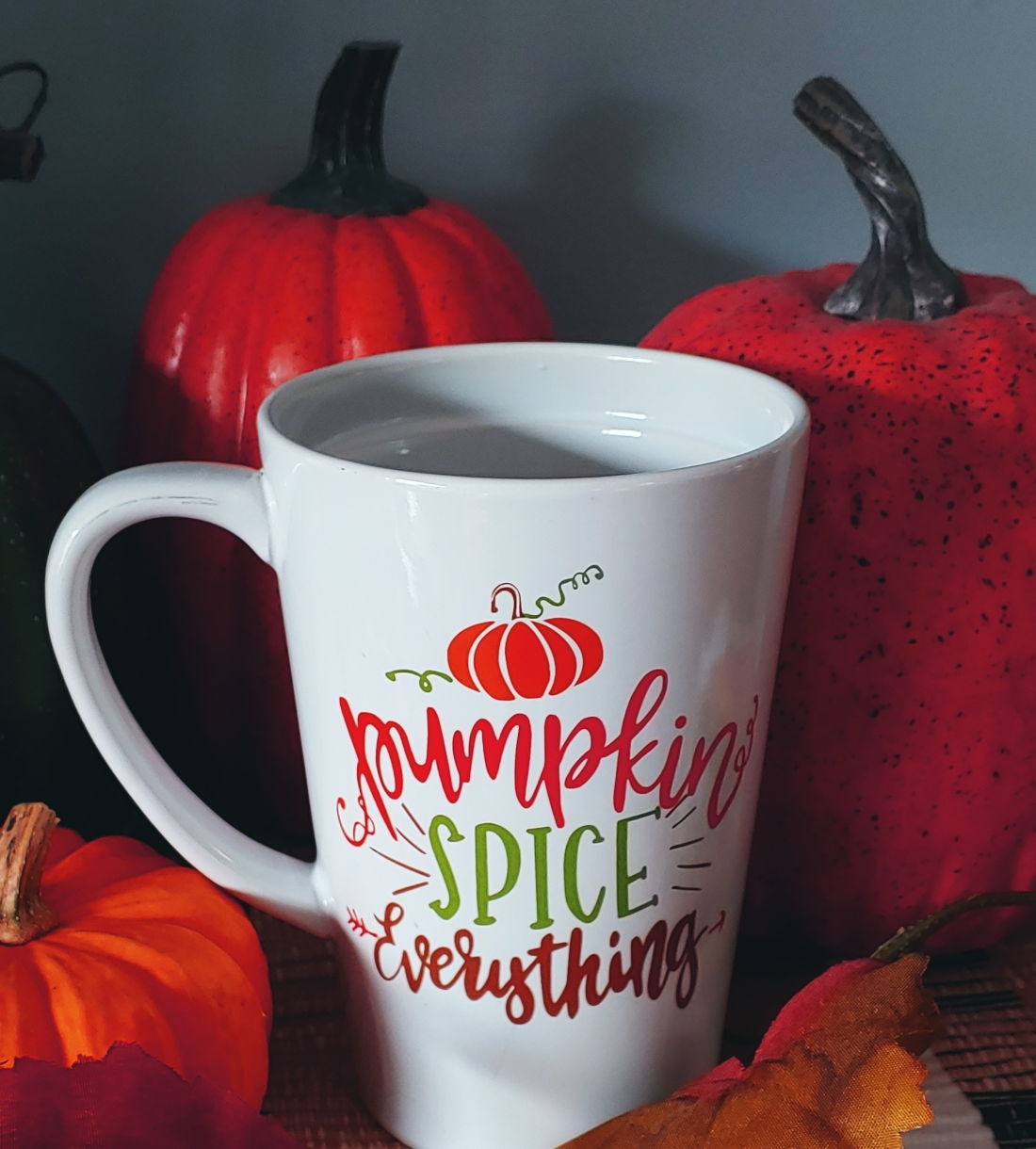 "A picture of a coffee mug that says, ""pumpkin spice everything"" surrounded by pumpkins"