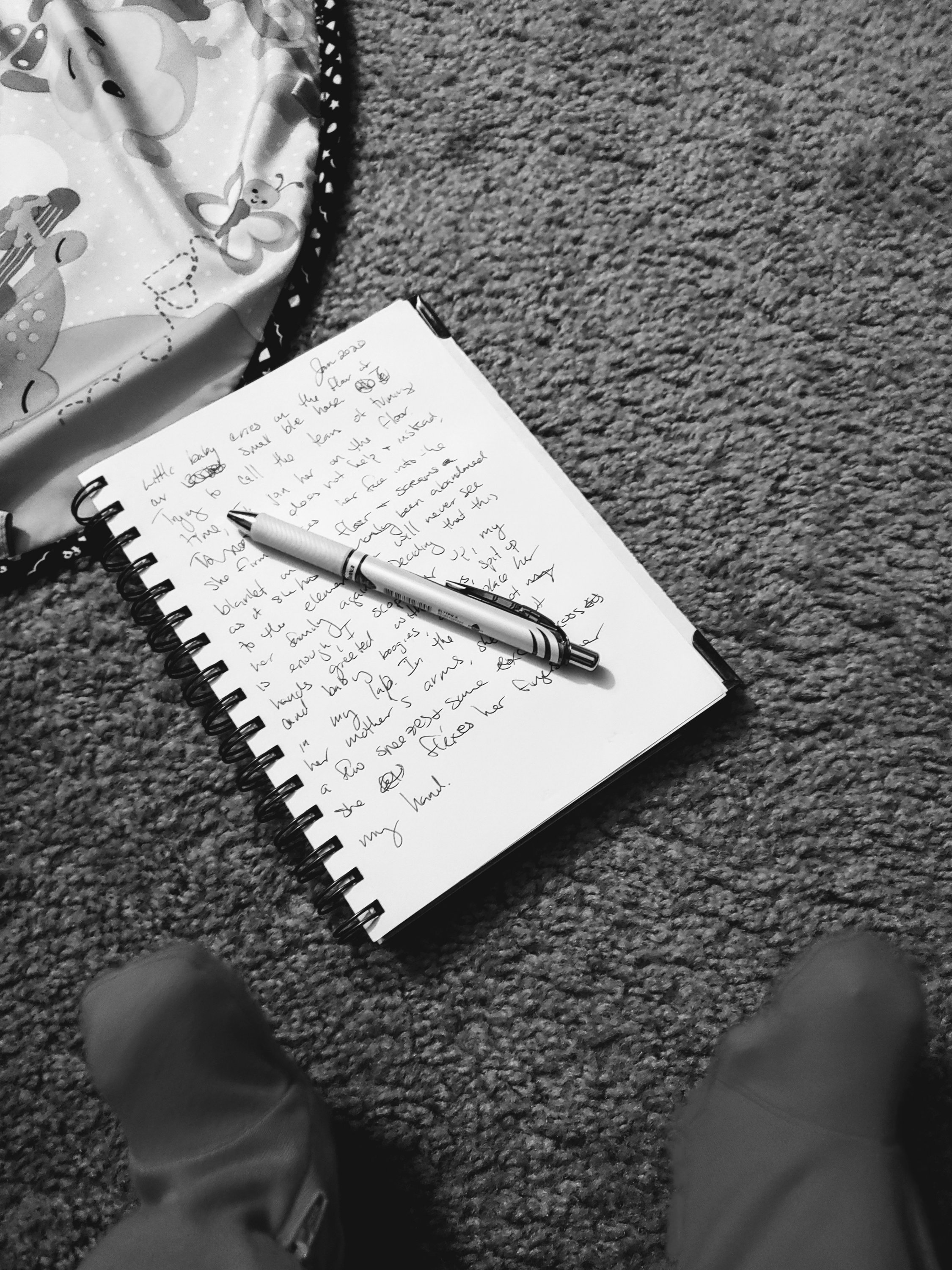Notebook, pen and baby feet