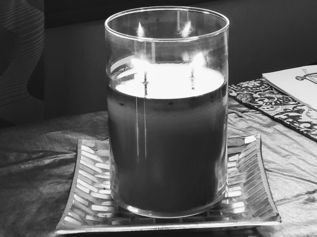 Candle on table in front of window